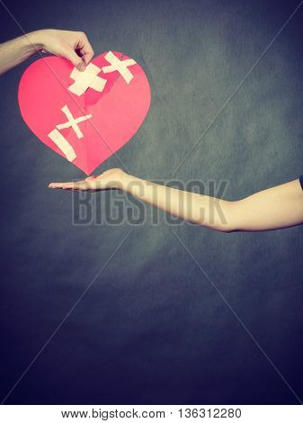 Woman And Man Hands Holds Broken Heart.