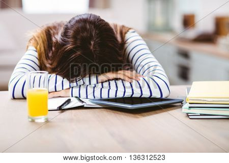 Close-up of woman napping with head by digital tablet and books on table