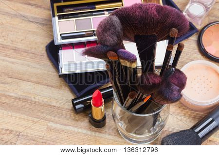 glass can with brushes and make up products on wooden table background