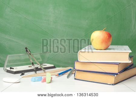 preparing supplies for school on the table next to chalk Board