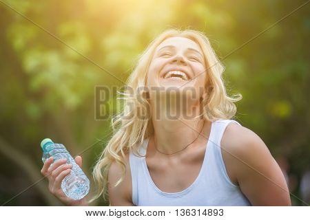 Girl with blond long hair walking in park with bottle of water and have fun. Image with lens flare effect