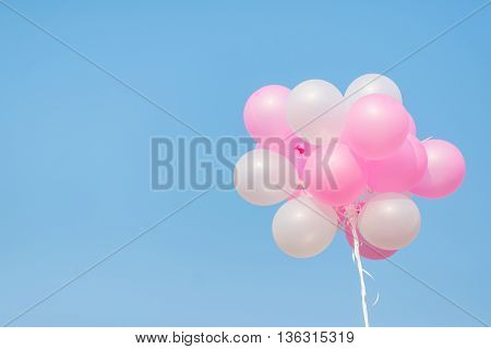 Pink and white balloon on blue sky with copy spacer
