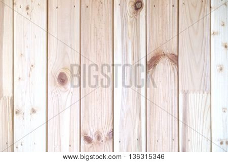 Wall from vertical sandy brown vertical oriented wooden planks as background horizontal view closeup