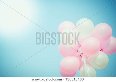 Pink and white balloon on blue sky with copy space