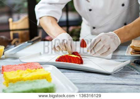 Hands touch slices of strawberry. Plate with pieces of berry. Flan with fresh strawberry. Pastry chef at work.