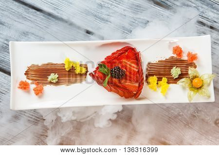 Dessert with strawberry on plate. Smoke around plate with dessert. Sliced berry and colorful bread. Tasty strawberry flan.
