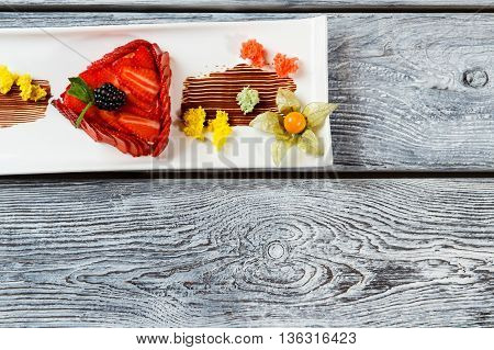 Dessert with strawberries on plate. Small pieces of colorful bread. Top view of dessert. Strawberry flan with mint leaf.