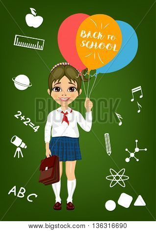 little girl in school uniform holding balloons with back to school text standing in front of school items on a blackboard