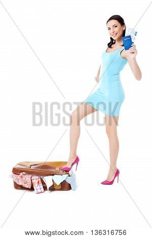 Travel concept. Portrait of stylish beautiful young woman wearing high heels shoes. Isolated on white background. Woman with suitcase full of clothes smiling, holding tickets and looking at camera