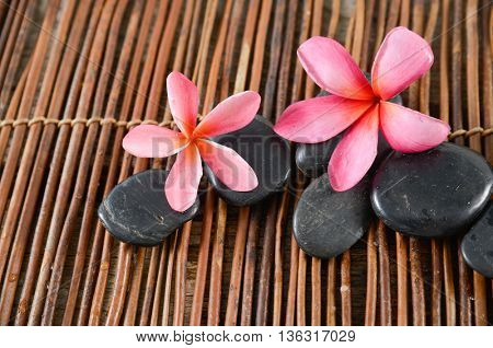 frangipani, black stones on mat