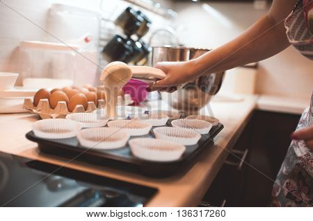 Woman cooking cupcakes closeup. Pouring batter in baking dish on table. Selective focus.