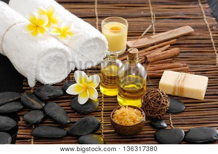 Spa setting with Frangipani with oil ,stones ,towel, soap with mat