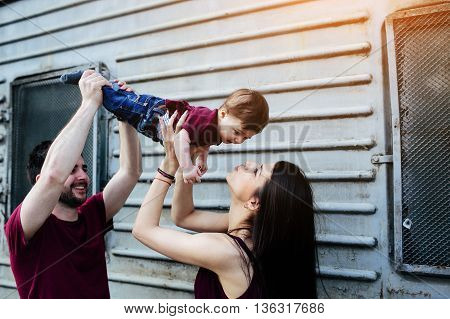 young beautiful family with child posing on the building background