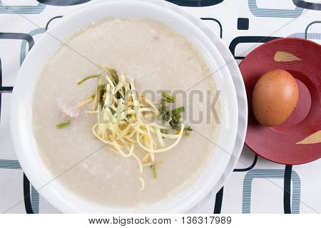 Traditional chinese porridge rice gruel in bowl with pork / Top view