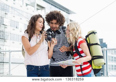 Friends holding map looking into camera on terrace