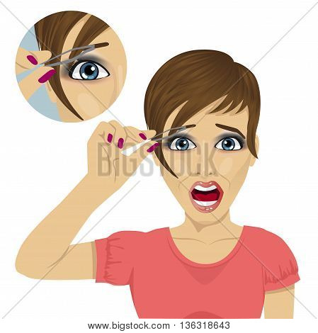 Young beautiful woman plucking her eyebrows with tweezers with a shout of pain over white background