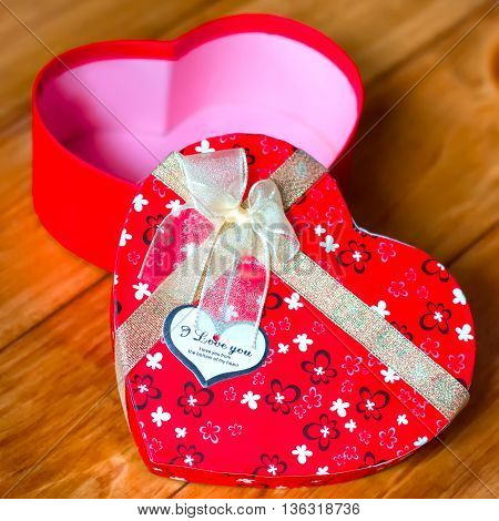 Gift box with heart shape with inscription i love you on wooden background. Square format.