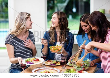Happy friends having food at table