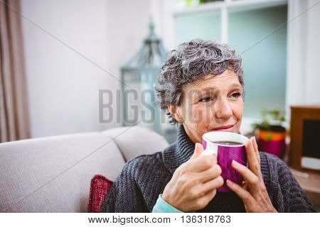Thoughtful mature woman holding coffee cup at home