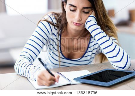 Close-up of young woman writing in notepad while sitting at table