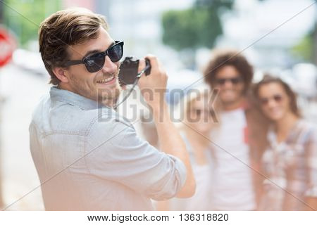 Man smiling at camera while taking photo of his friends