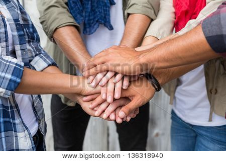 Friends putting their hands together outdoors