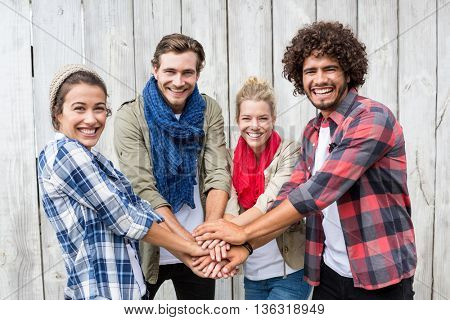 Portrait of friends putting their hands together