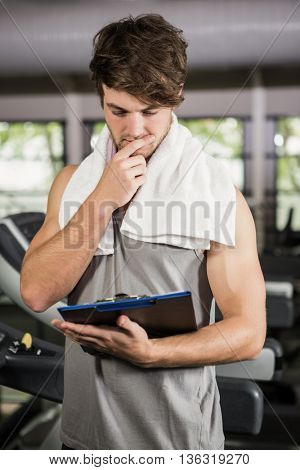 Gym instructor looking at clipboard in gym