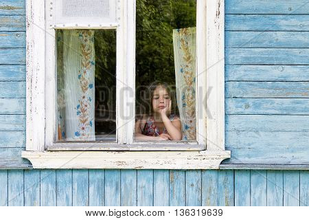 Sad little girl looking out the country house window leaning her face on her hand. Outside view