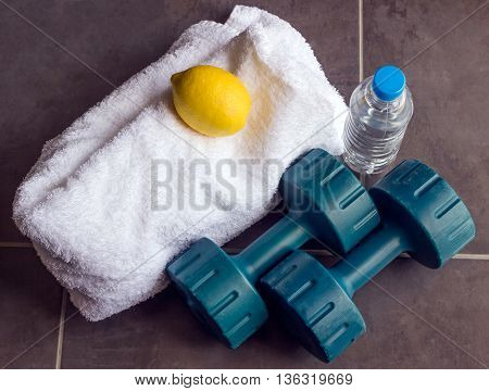 Concept - sports. Dumbbells are next to a white towel bottle of water and lemon.