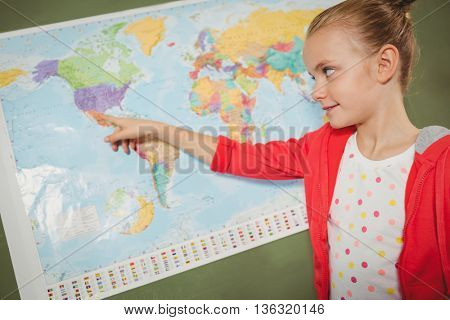 Girl pointing on world map at school