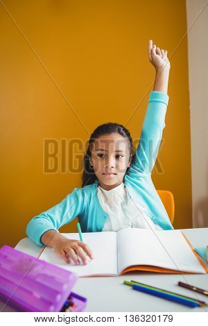 A serious girl rising her hand at school