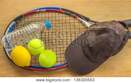 Concept - sport. Tennis rackets and balls are next to a bottle of water lemon and a baseball cap.
