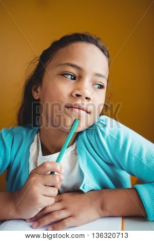 Thoughtful girl sitting at a desk at school
