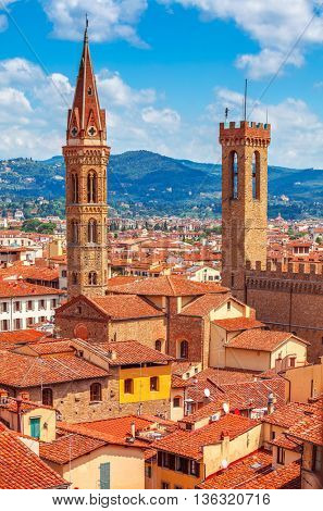 Tower of palazzo vecchio in florence top view to tile roofs old town blue mountains landscape on background italy