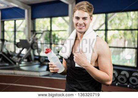 Portrait of man holding a water bottle at gym