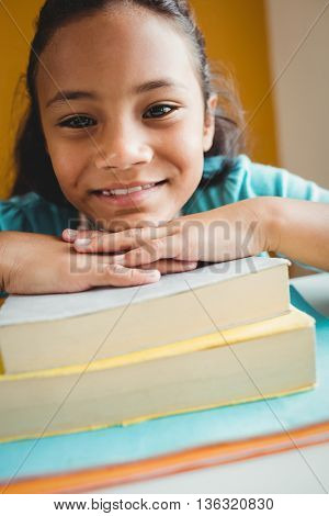 Girl leaning her head on pile of books at school