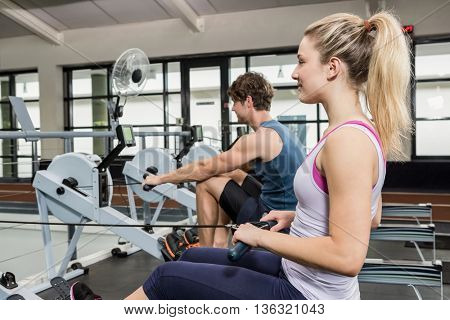 Man and woman working out on rowing machine at gym
