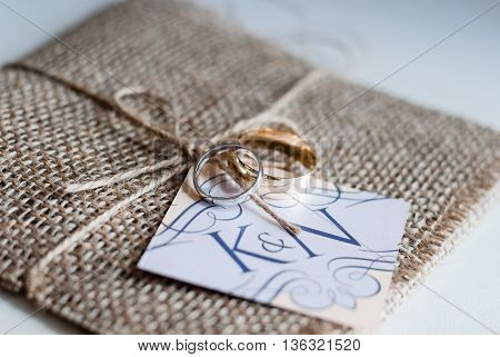 hessian wrapped wedding invitation with rings sitting on top