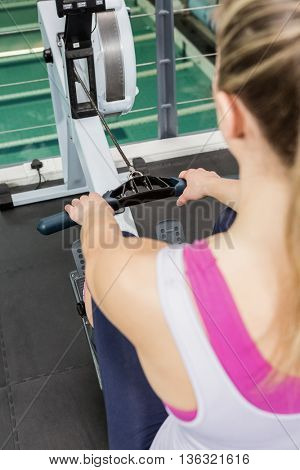 Woman exercising on rowing machine at gym