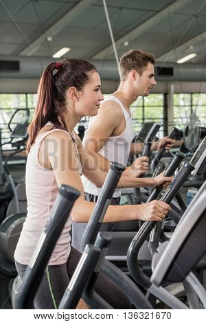 Beautiful woman and man exercising on the elliptical machine at gym