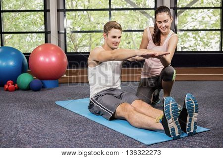 Trainer assisting man with abdominal crunches at gym