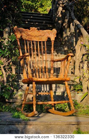Antique Italian Carved wooden rocking chair in the garden