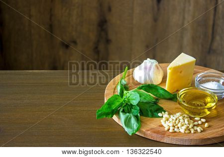 Sicilian basil pesto ingredients on wooden table with copypaste space