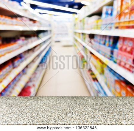 Marble board empty table in front of blurred background. Perspective marble table over blur of baby foods jars in store. Mock up for display or montage your product.