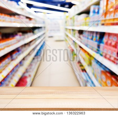 Wooden board empty table in front of blurred background. Perspective light wood table over blur of baby foods jars in store. Mock up for display or montage your product.