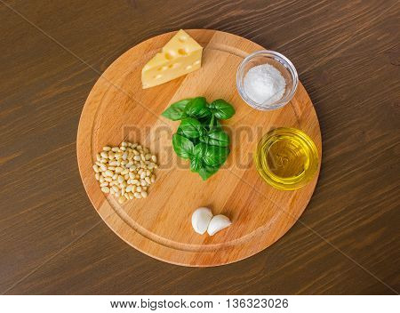 Sicilian basil pesto ingredients on wooden table. front