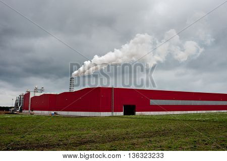 Smoking industrial pipes. red shed with a chimney and smoke