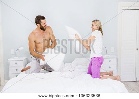 Couple having a pillow fight in bed at bedroom