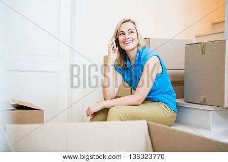 Smiling young woman talking on mobile phone in new house